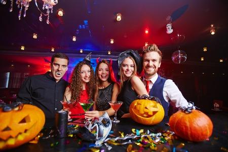 calabazas de halloween: Los jóvenes que presentan en los sombreros de Halloween con calabazas y Foto de archivo