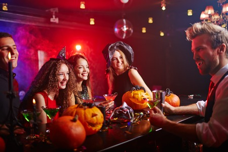 bartender: Disguised vampire serving drinks to witches at Halloween night