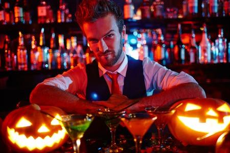 Camarero de la noche de Halloween mirando calabaza