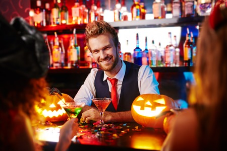 Young handsome bartender working at Halloween Stock Photo
