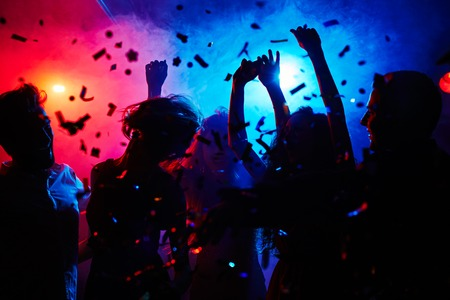 menschenmenge: Silhouetten von Tänzern bewegt in Konfetti