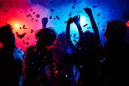 fiesta: Siluetas de los bailarines se mueven en confeti