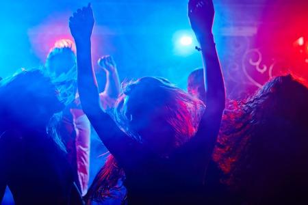 Active friends dancing in spotlights