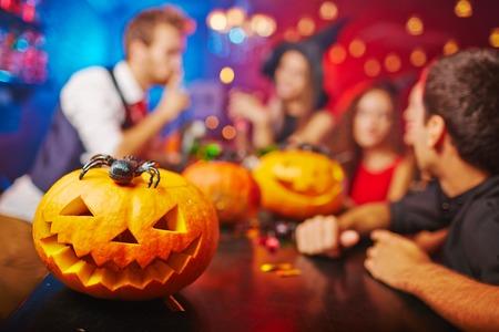 pumpkin: Jack-o-linterna en barra de bar y amigos en el fondo Foto de archivo
