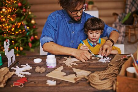 Young man showing his little son how to paint wooden xmas toys