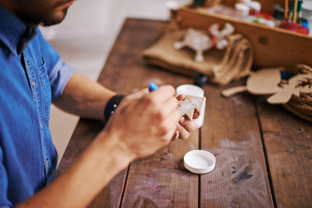firtree: Man painting wooden firtree with white gouache Stock Photo