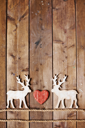holiday tradition: Two reindeers on ropes and red heart between them on wooden background Stock Photo