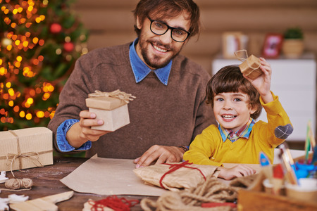 christmastide: Happy young man and little boy with giftboxes looking at camera