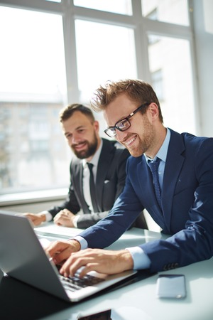 Smiling businessman browsing on laptop with co-worker on background