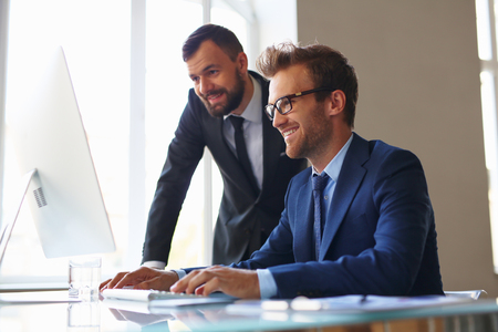 Two businessmen working with computer in office
