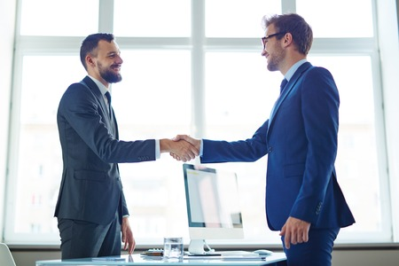 young man: Confident businessmen handshaking over workplace in office Stock Photo