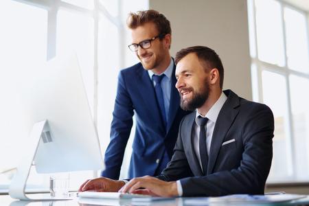 persona alegre: Dos hombres de negocios exitosos que usan el ordenador en la reunión Foto de archivo
