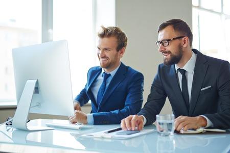 ejecutivos: Empresarios modernos consultoría en frente de la computadora en la reunión