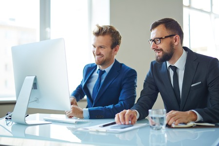 Modern businessmen consulting in front of computer at meeting