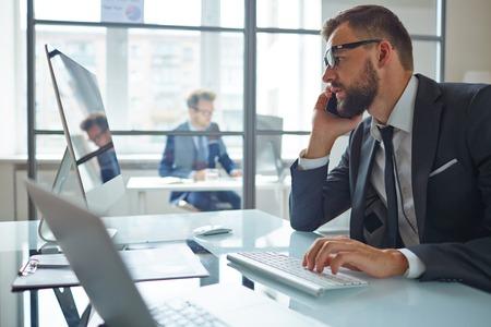 オフィスのコンピューターの前に座っている間に電話で現代ビジネスマン コンサルティング パートナー
