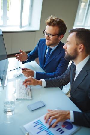 tecnologias de la informacion: Hombres de negocios modernos en discusiones datos delante de la computadora en la oficina Foto de archivo
