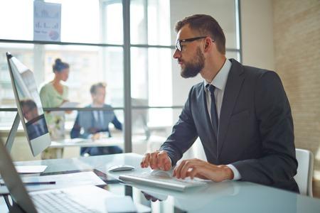 hombre con barba: Empleado joven que mira el monitor de la computadora