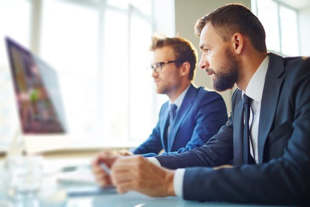 busy beard: Young businessman looking at computer monitor with colleague near by Stock Photo
