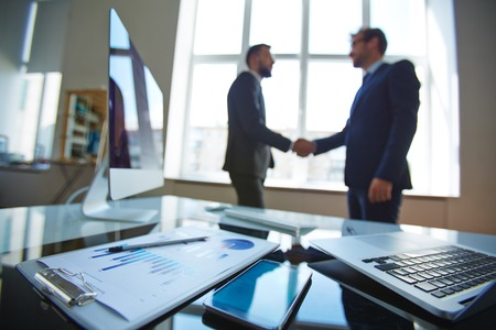 Business objects at workplace with businessmen handshaking on background. Stock Photo