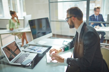 trabajo oficina: Empleado joven que mira el monitor de la computadora durante la jornada de trabajo en la oficina