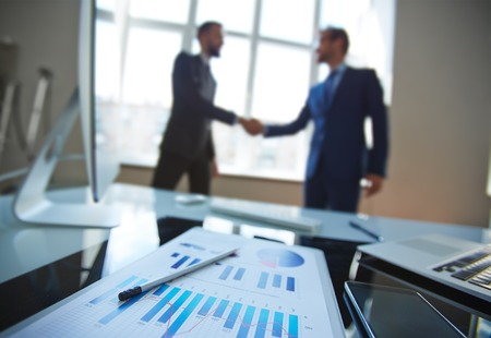 handshaking: Business document at workplace with business partners handshaking on background Stock Photo
