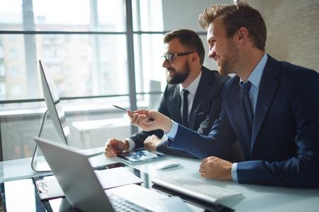 자신감이 사업가 그의 동료 상담 및 회의에서 컴퓨터 모니터를 가리키는