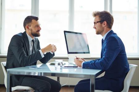 相談時にテーブルに座っている自信を持っているビジネスマン 写真素材