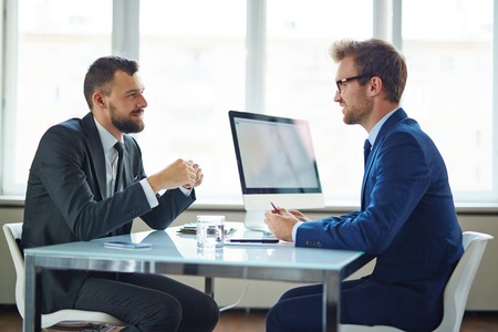 consulting: Confident businessmen sitting by table during consultation Stock Photo