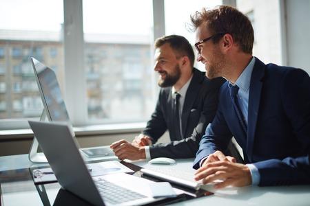 reuniones empresariales: Sonriente hombre de negocios y su colega mirando el monitor del ordenador en la reuni�n Foto de archivo
