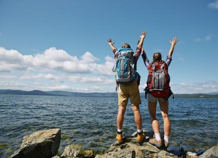 mochila de viaje: Par de los viajeros con los brazos levantados que disfrutan de vacaciones de verano junto al mar Foto de archivo