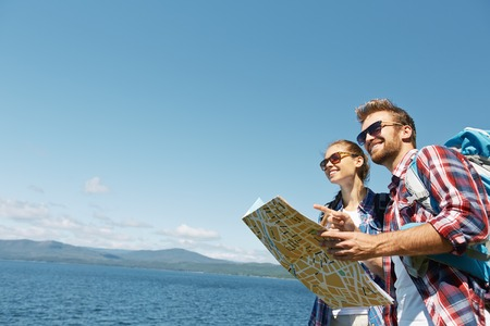 Amorous hikers with map on background of the sea Stock Photo