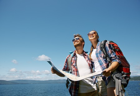 looking upwards: Cheerful hikers with map looking upwards against blue sky Stock Photo