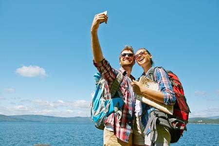 mochila viaje: Excursionistas alegres haciendo selfie durante el viaje contra el cielo azul