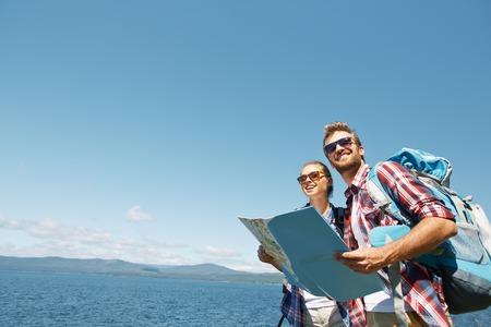 空と海の背景に彼らの旅行を楽しむマップと陽気なハイカー