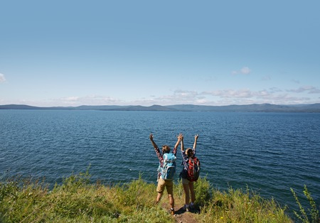 ecstatic: Ecstatic hikers with raised arms standing by the sea Stock Photo