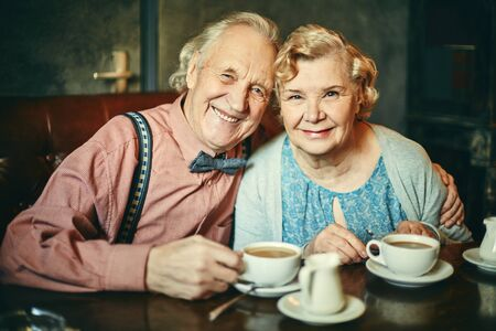 women coffee: Happy retired couple having tea in cafe