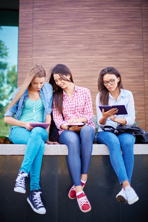 touchpad: Group of college girlfriends with touchpad and notepads outdoors