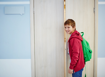 door: Cute boy with backpack looking at camera while opening classroom door