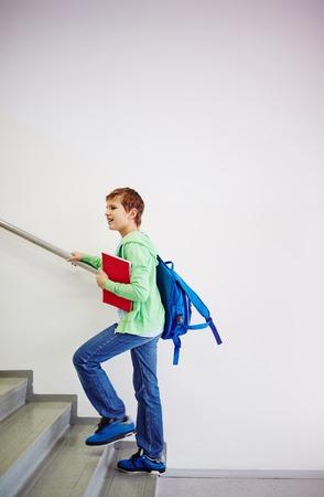 upstairs: Pre-teen schoolboy with backpack going upstairs in school