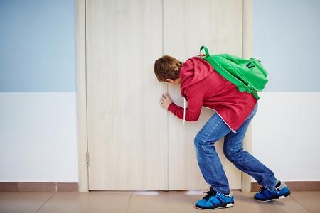 peeping: Curious pupil peeping into keyhole of classroom door at school