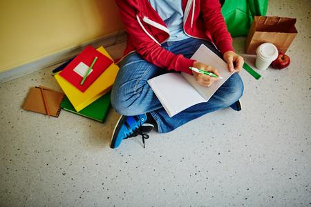 niños escribiendo: Colegial haciendo notas en el ejercicio-libro mientras está sentado en el suelo