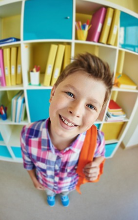 schoolkid: Cute schoolkid with backpack looking at camera Stock Photo