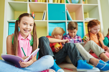 elementary schools: Cute schoolgirl with exercise-book looking at camera with classmates on background Stock Photo
