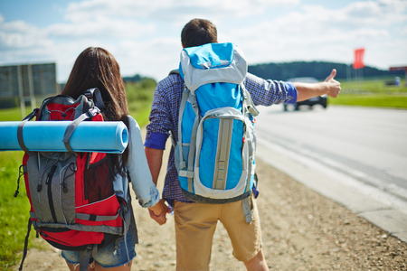 rucksacks: Young couple of travelers with rucksacks hitch-hiking by road
