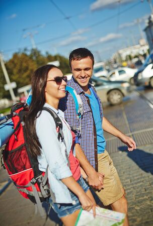 rucksacks: Young hikers with rucksacks sightseeing in a city Stock Photo