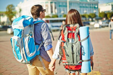 rucksacks: Affectionate travelers with rucksacks walking down unknown city