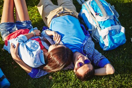 amorous: Two amorous travelers having rest on green grass