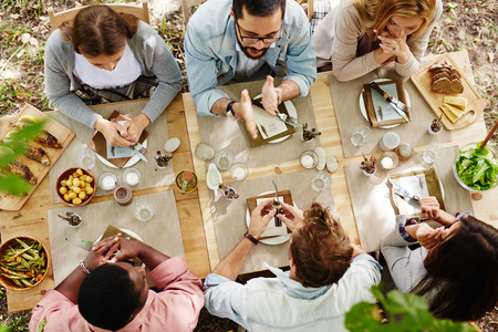 feasts: Group of young friends gathered at Thanksgiving dinner table