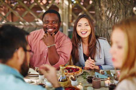 thanksgiving adult: Happy young couple looking at camera by Thanksgiving table