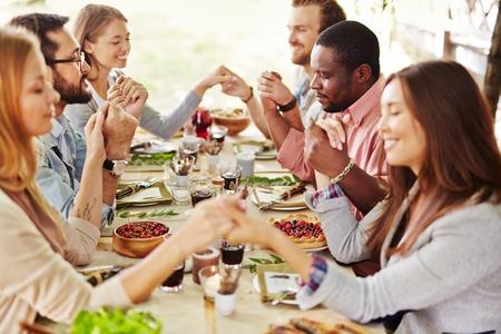 amigos: Grupo de jóvenes amigos en la mesa de Acción de Gracias rezando